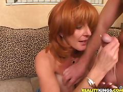 Redhead MILF with big tits gives a titjob and rides a cock